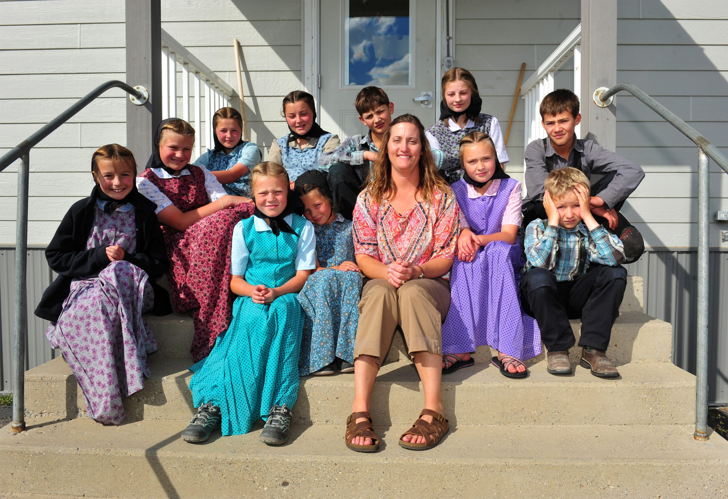 Traci Manseau sits with her class on the steps of their one-room school on the Deerfield Hutterite Colony. Manseau is a teaching veteran of 23 years and she has spent her entire career teaching in one room rural school houses.