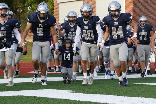 Troy Ross, 4, leads the Great Falls High Bison onto the field last Friday night at Memorial Stadium.