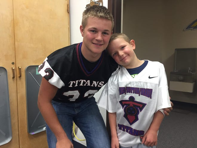 Peyton Hill and 6-year-old Calvin Diekhans of Power are good buddies. Hill and his Power-Dutton-Brady teammates will honor the little cancer survivor on Saturday afternoon.