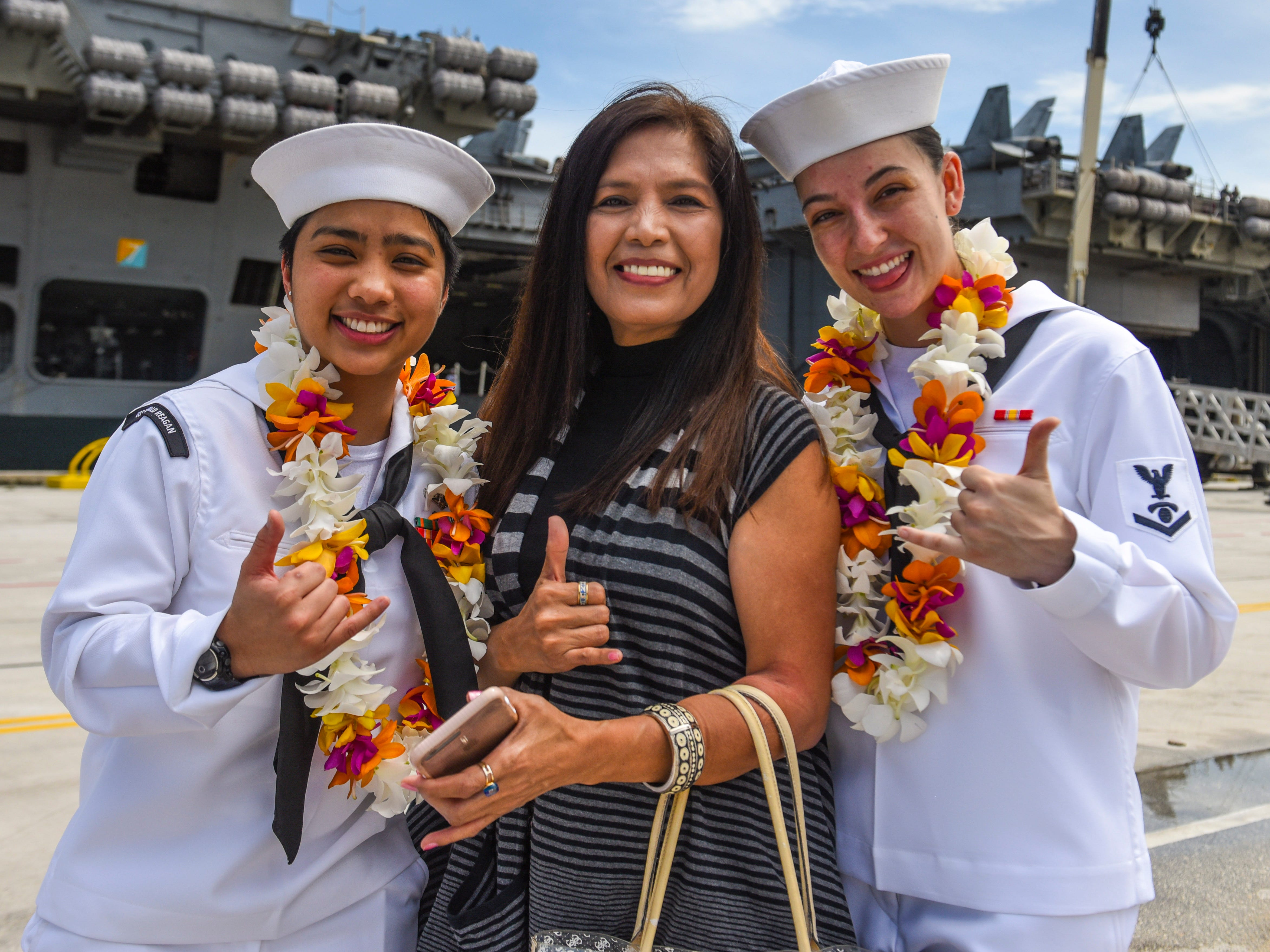 Janet Steele, center, is flanked by her niece, Petty Officer 2nd Class Jeanalynn Samson, left, and Petty Officer 3rd Class Stephanie Walsh, after the sailors' arrival aboard the Nimitz-class nuclear-powered aircraft carrier, USS Ronald Reagan, at the Kilo Wharf on Naval Base Guam in Sumay, on Monday, Sept. 24, 2018.