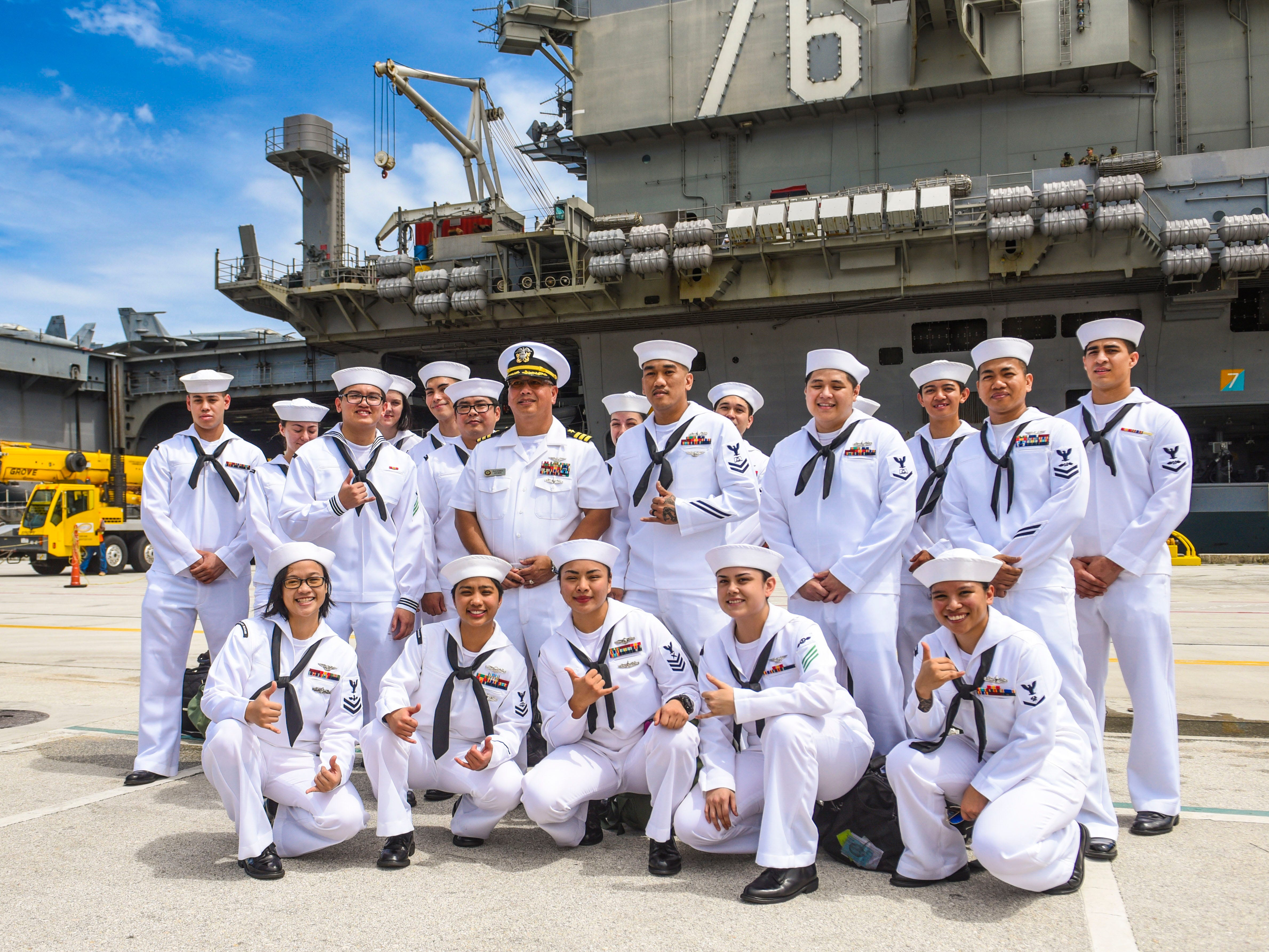 Nineteen sailors with Guam ties, serving aboard the Nimitz-class nuclear-powered aircraft carrier, USS Ronald Reagan, gather for a group photo after the ship docked at the Kilo Wharf on Naval Base Guam in Sumay on Monday, Sept. 24, 2018. The vessel and its crew of nearly 5,000 sailors, normally forward-deployed at Yokosuka, Japan, is paying a port visit to the island.