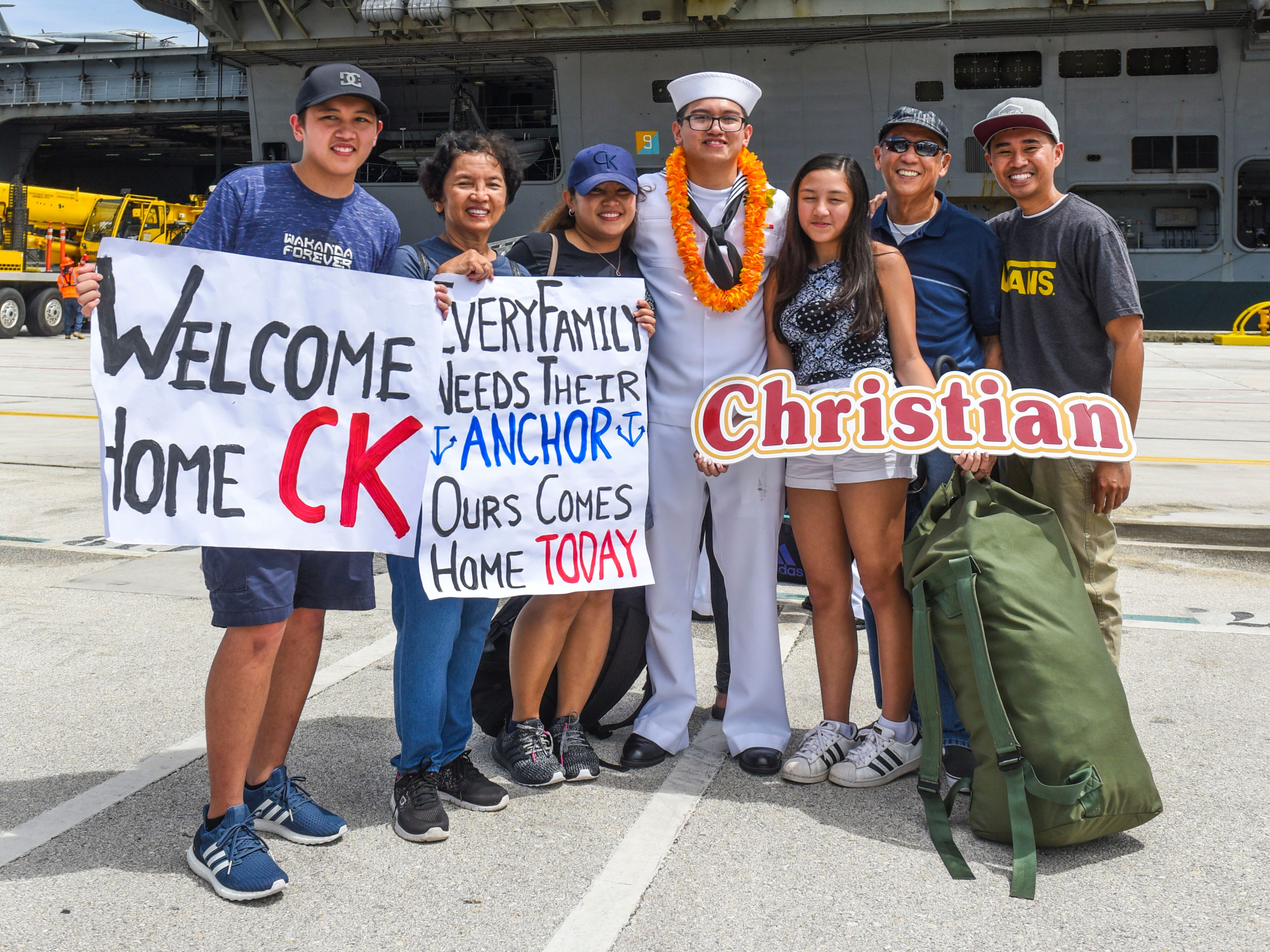 Navy Airman Christian Dela Cruz, center, is greeted by family members after his arrival aboard the Nimitz-class nuclear-powered aircraft carrier, USS Ronald Reagan, at the Kilo Wharf on Naval Base Guam in Sumay, on Monday, Sept. 24, 2018.