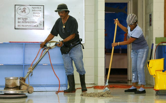 In this file photo, custodian supervisor Anthony Camacho, left, and school aide III Pat Aguon, right, clean classrooms at Agueda I. Johnston Middle School in Ordot.