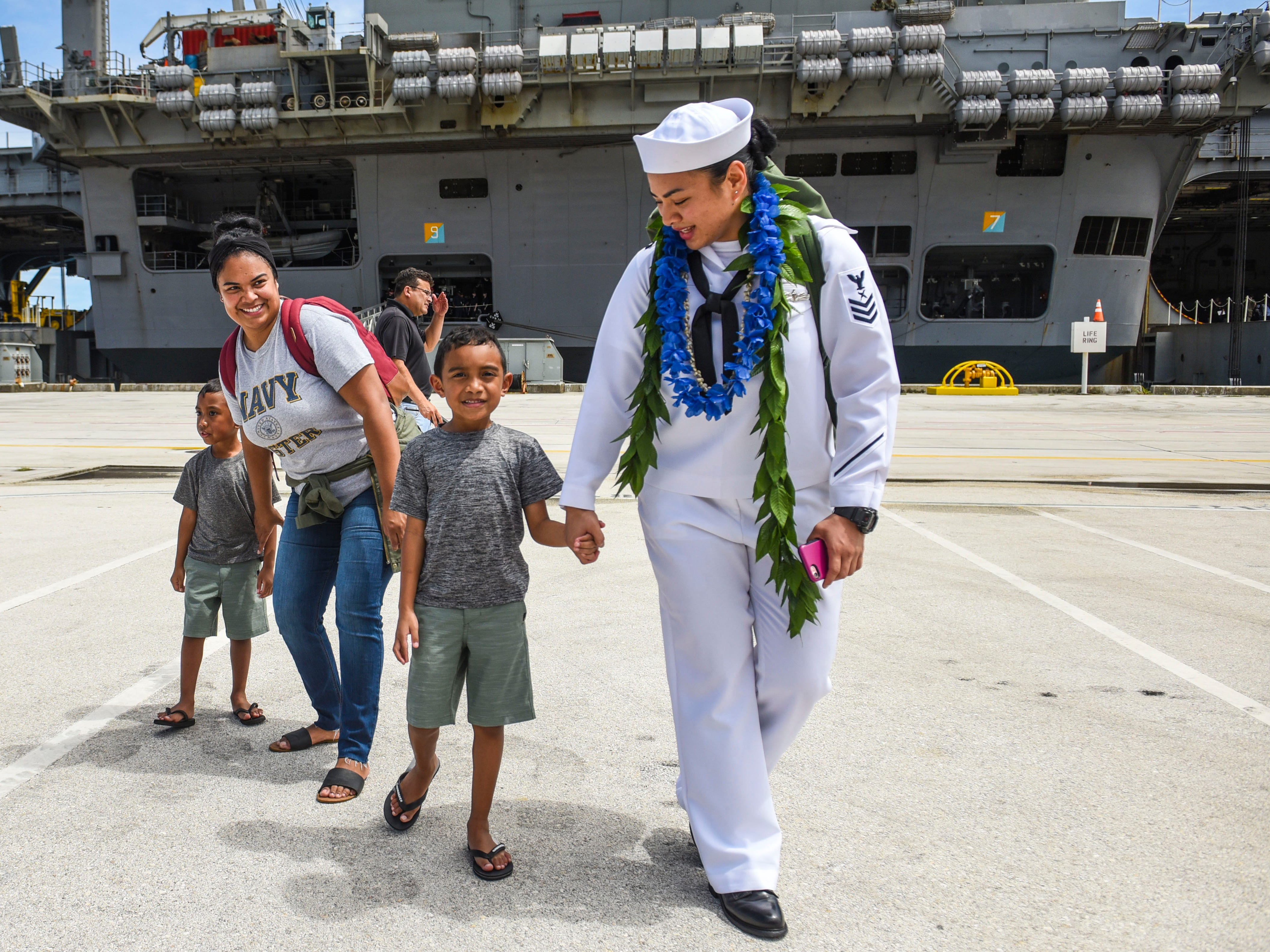 Petty Officer 1st Class Tiyana Cruz, right, walks with her godson, Brayden, and other family members after her arrival aboard the Nimitz-class nuclear-powered aircraft carrier, USS Ronald Reagan, at the Kilo Wharf on Naval Base Guam in Sumay on Monday, Sept. 24, 2018. The vessel and its crew of nearly 5,000 sailors, normally forward-deployed at Yokosuka, Japan, is paying a port visit to the island.