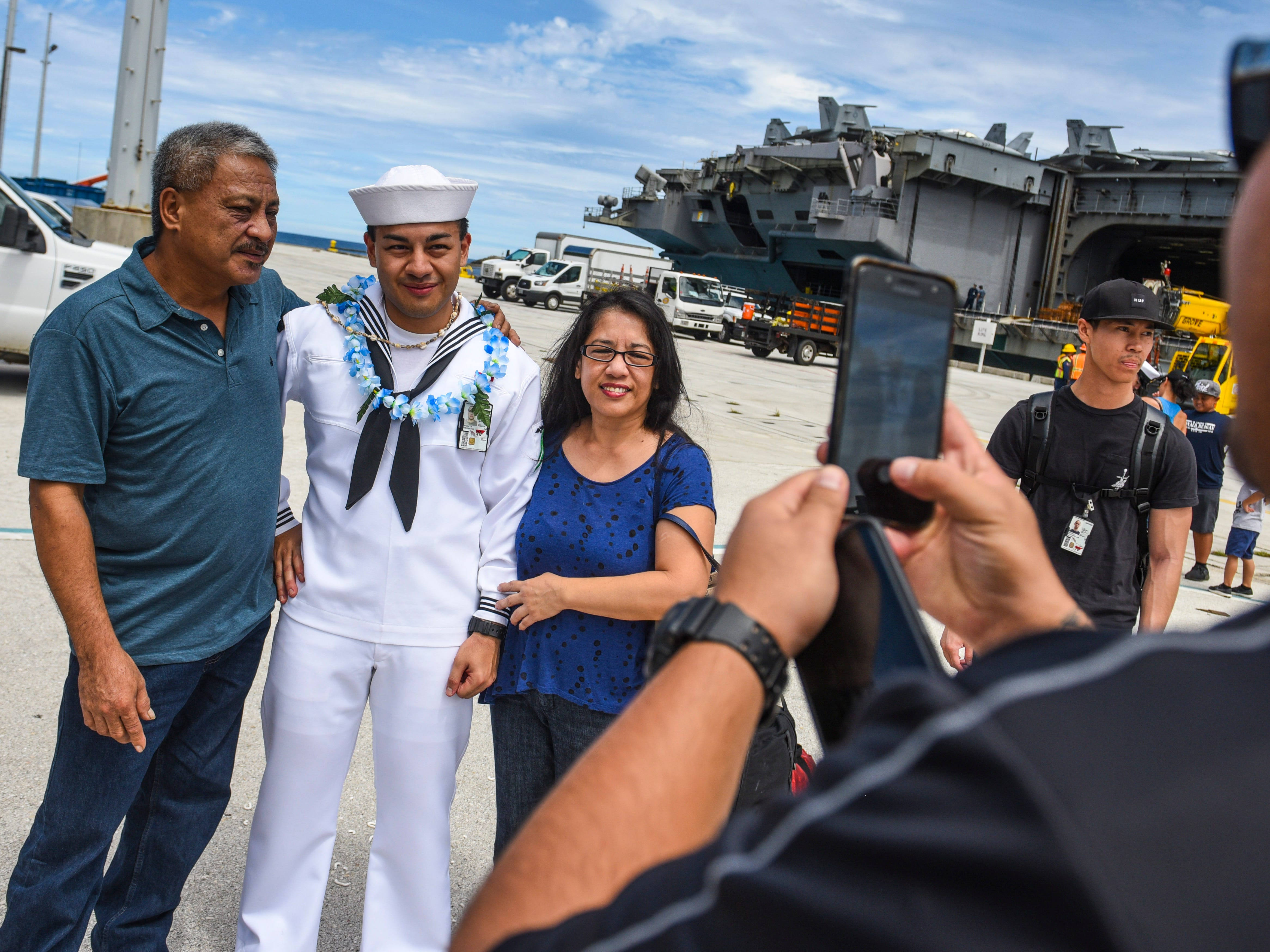 Airman Jason Ungacta, is greeted by his parents, Paul, left, and Rena Ungacta, and other family members after his arrival aboard the Nimitz-class nuclear-powered aircraft carrier, USS Ronald Reagan, at Kilo Wharf on Naval Base Guam in Sumay, on Monday, Sept. 24, 2018.