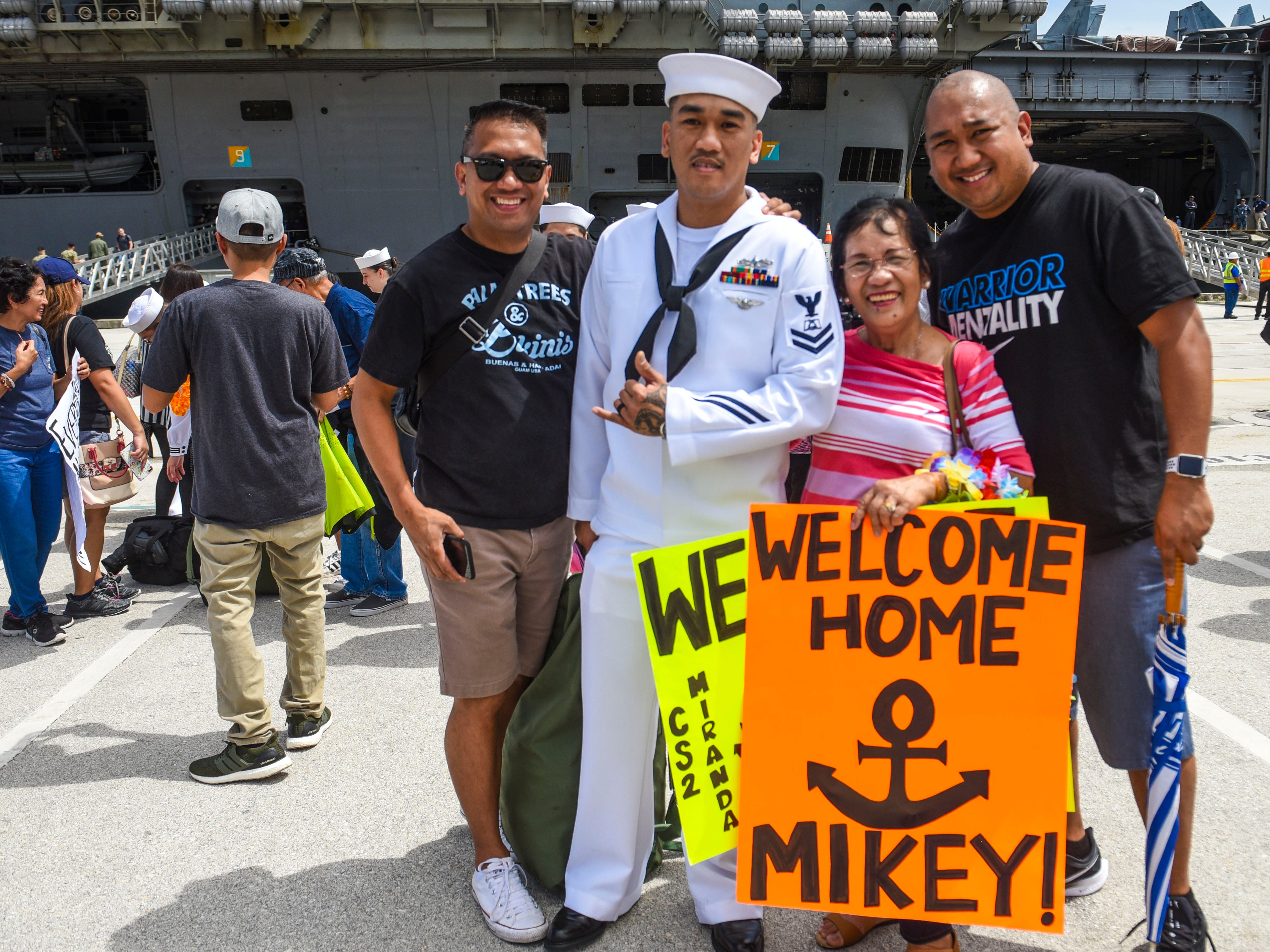 Petty Officer 2nd Class Mike Miranda is photographed with his mother, Ida Miranda, and brothers, Romy and Jun, right, Miranda after his arrival aboard the Nimitz-class nuclear-powered aircraft carrier, USS Ronald Reagan, at Kilo Wharf on Naval Base Guam in Sumay, on Monday, Sept. 24, 2018.