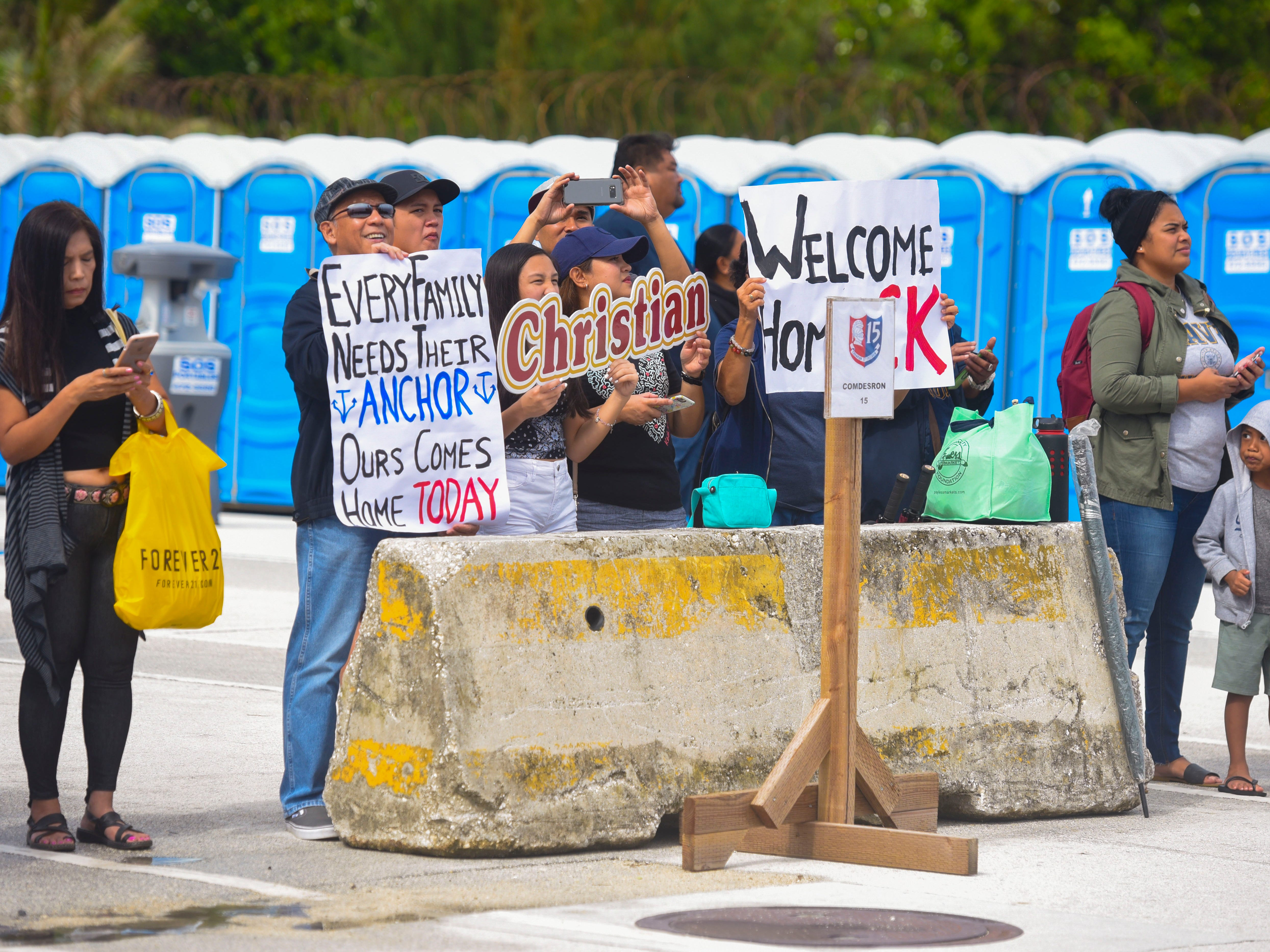 Family members of Navy Airman Christian Dela Cruz anxiously await for his arrival and other sailors aboard the Nimitz-class nuclear-powered aircraft carrier, USS Ronald Reagan, as the vessel pulls into the Kilo Wharf at Naval Base Guam in Sumay, on Monday, Sept. 24, 2018.