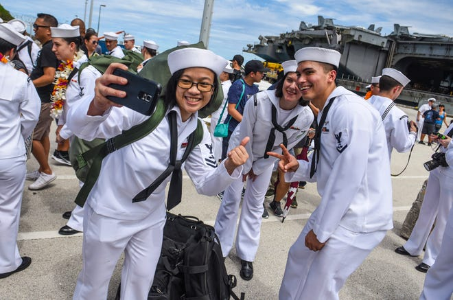 Sailors from the Nimitz-class nuclear-powered aircraft carrier USS Ronald Reagan are greeted by family and friends during their arrival at the Kilo Wharf on Naval Base Guam in Sumay Sept. 24.