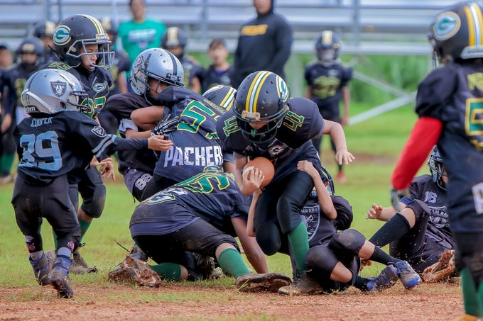Tristen Ray Martinez (41) of Packers tries to evade a tackle by a Raiders player during Guam National Youth Federation Manha Division football game match held at the Raiders field in Tiyan on Sept. 23.