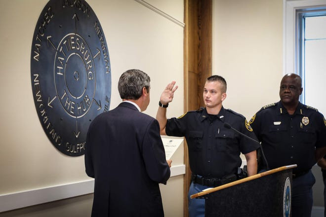 Newly sworn police officer Jared Barnard is administered the oath of office Hattiesburg Mayor Toby Barker while Police Chief Anthony Parker watches.