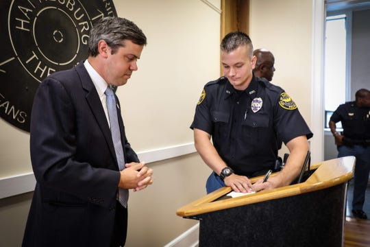 Newly sworn police officer Jared Barnard signs paper work after Hattiesburg Mayor Toby Barker administers the oath of office.