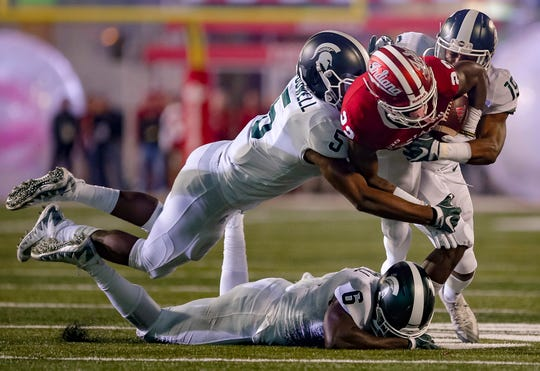 Whop Philyor #22 of the Indiana Hoosiers is tackled while rushing by Andrew Dowell #5 and Josh Butler #19 of the Michigan State Spartans during the game at Memorial Stadium on September 22, 2018 in Bloomington.