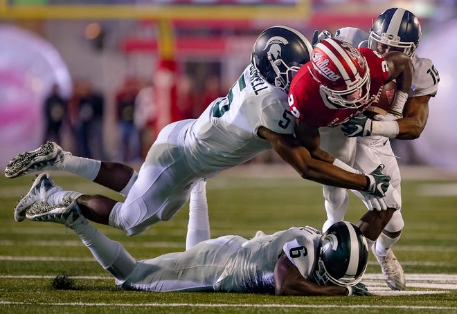 IU's Whop Philyor was tackled while rushing by Andrew Dowell #5 and Josh Butler #19 of the Michigan State Spartans during their game Saturday in Bloomington.