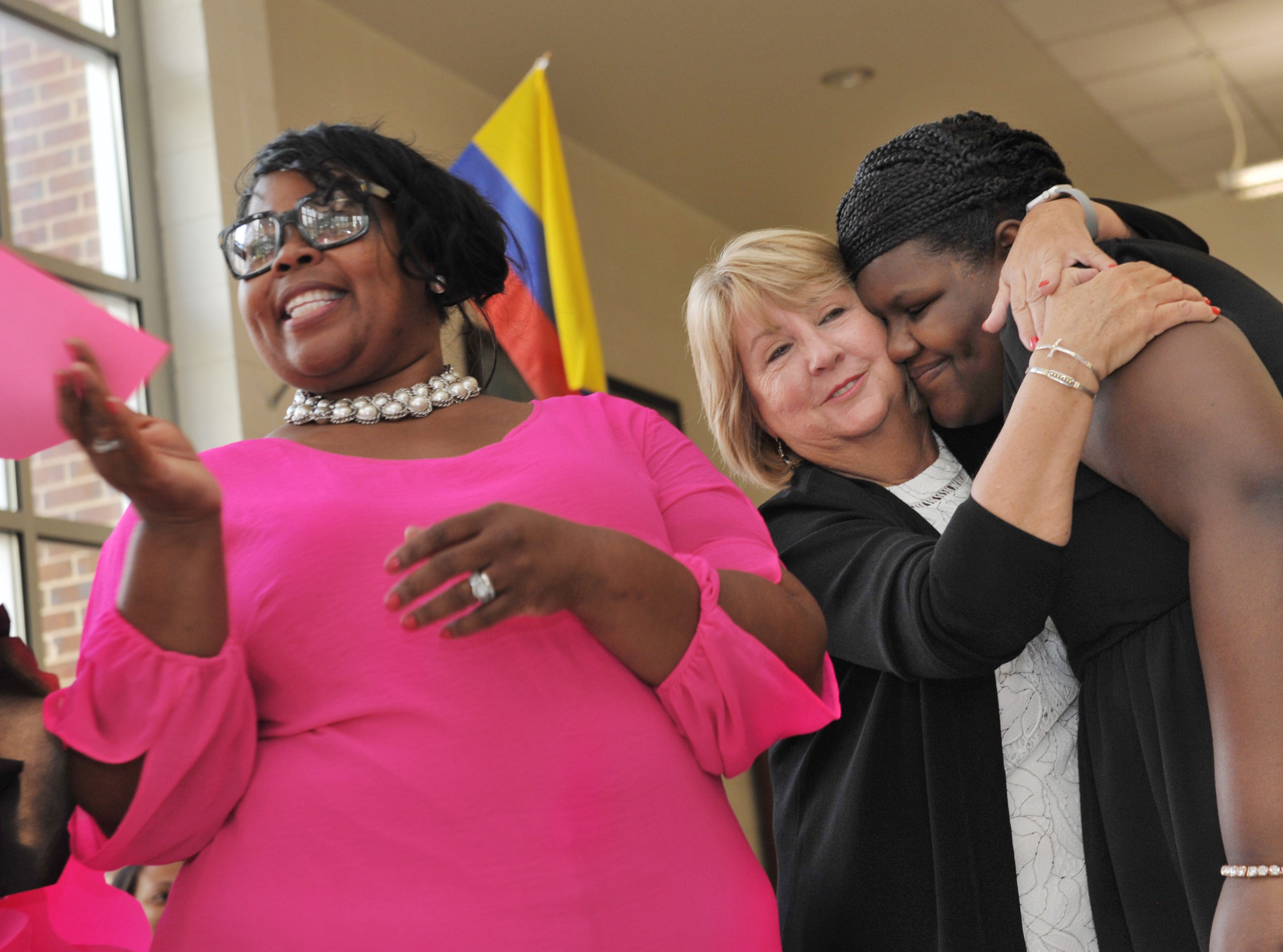 As Karen Goodman, from left, cosponsor of Highland Elementary Girls with Purpose Club, gets ready to hand out the next active membership certificate, Mississippi First Lady Deborah Bryant gives Highland Elementary 5th grader D'Kirah Stribling, 10, a hug during the Girls with Purpose Club Mother-Daughter Tea at the Ridgeland school.