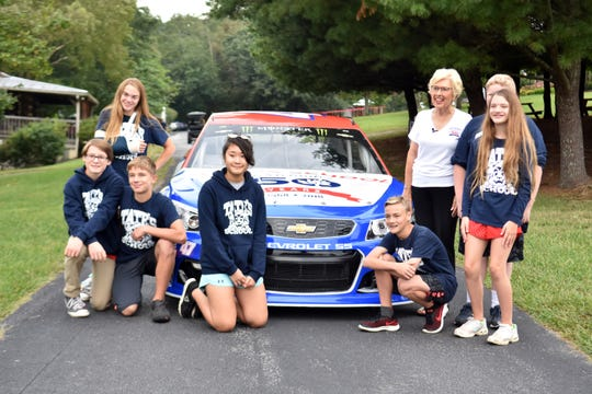 Eighth grade students at Tate's School pose for photos with founder Lou L Tate in front of the racing car following the 50th anniversary at the school.