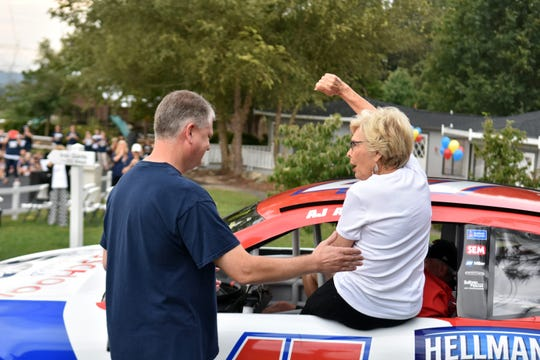 Tate's School founder Lou L Tate arrives at the 50th anniversary celebration in a race car.