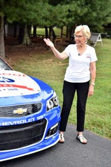 Tate's School founder Lou L Tate encourages students to stop by the race car for photos at the school's 50th anniversary celebration.
