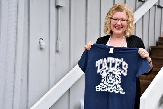 Paula Gunter, daughter of Tate's School founder Lou L and Joe Tate, shows one of the school T-shirts.