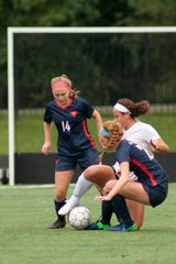 Sacred Heart defender-midfielder Caraline Francke, left, Sacred Heart forward-midfielder Estelle Gabriel, right, and Assumption forward Corinna Soto, center, battle for the ball.