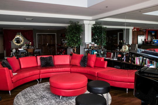 The large curving red sofa was rescued from a nightclub and provides a lot of seating for parties. A mirrored wall helps make the living room seem more expansive. Sept. 17, 2018.