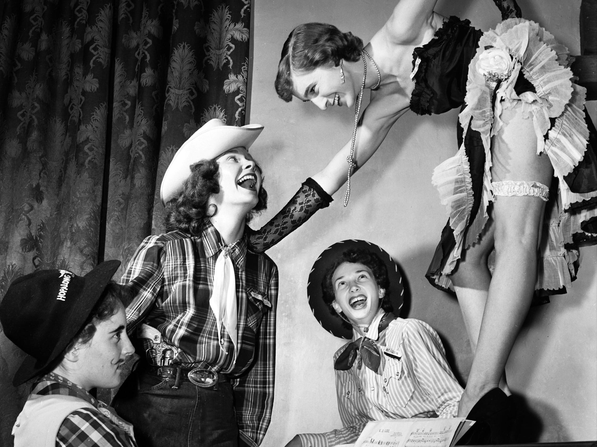 "Can-can girl Viola Deavours of San Antonio, TX leads a trio of rugged cowpokes (Left to Right), Helen Coke of Caruthersville, MO; Mary Taylor of Winston-Salem, NC and Ruth Faquin of 186 Mignon in a rousing chorus from a popular Western ditty.  The scene occurred at Kappa Delta Sorority's ""Pink Garter"" Western-type cafe  during sorority rush at Southwestern College on 27 Sep 1951."