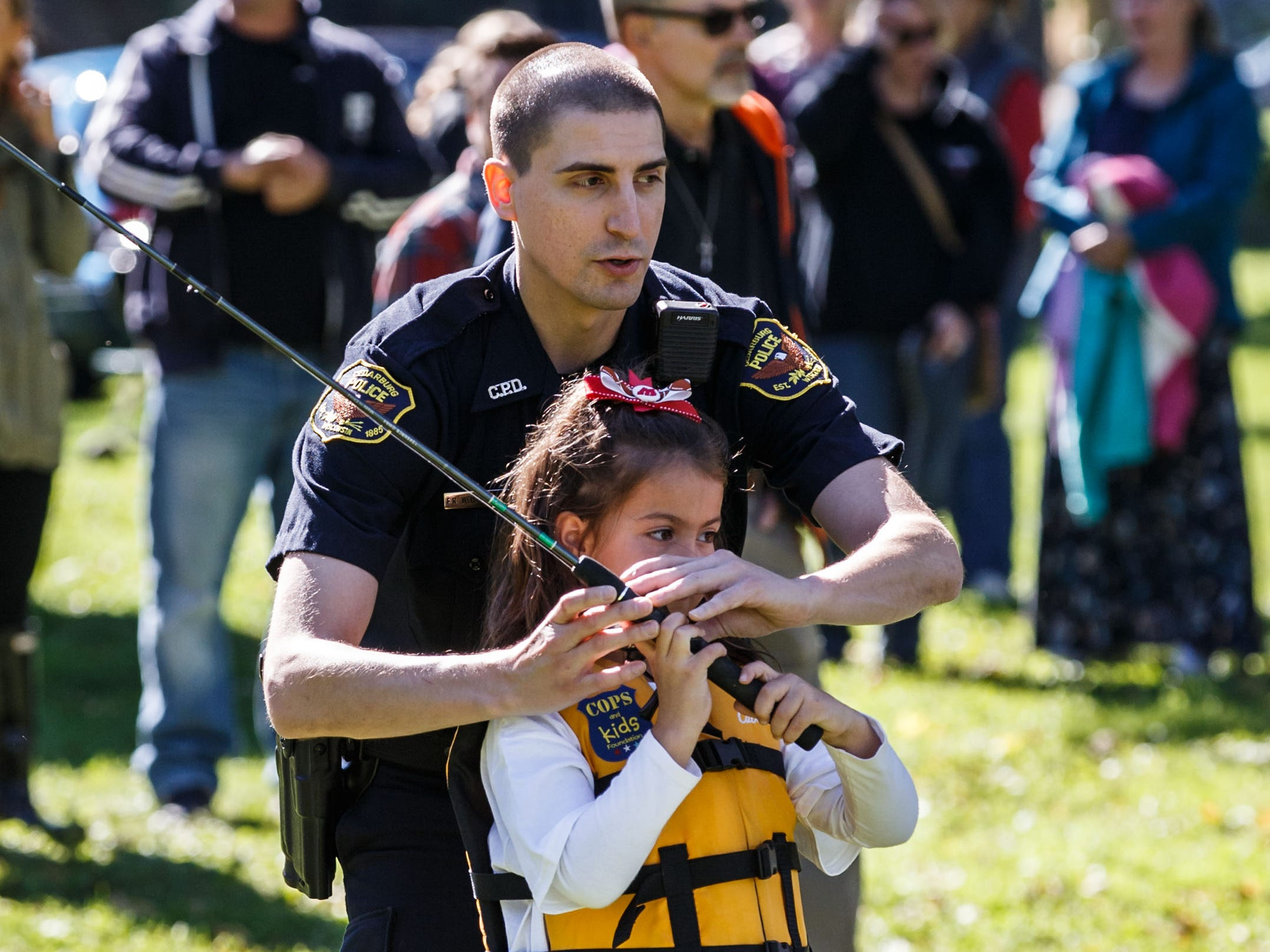 Cedarburg Police Officer Eric Weisenberger helps a youngster with her casting technique during the inaugural Cops & Bobbers fishing event hosted by Cedarburg Police Department at Cedar Creek Park on Saturday, Sept. 22, 2018. The free catch-and-release event provides children a fun opportunity to interact with law enforcement officers while learning fishing techniques and water safety.