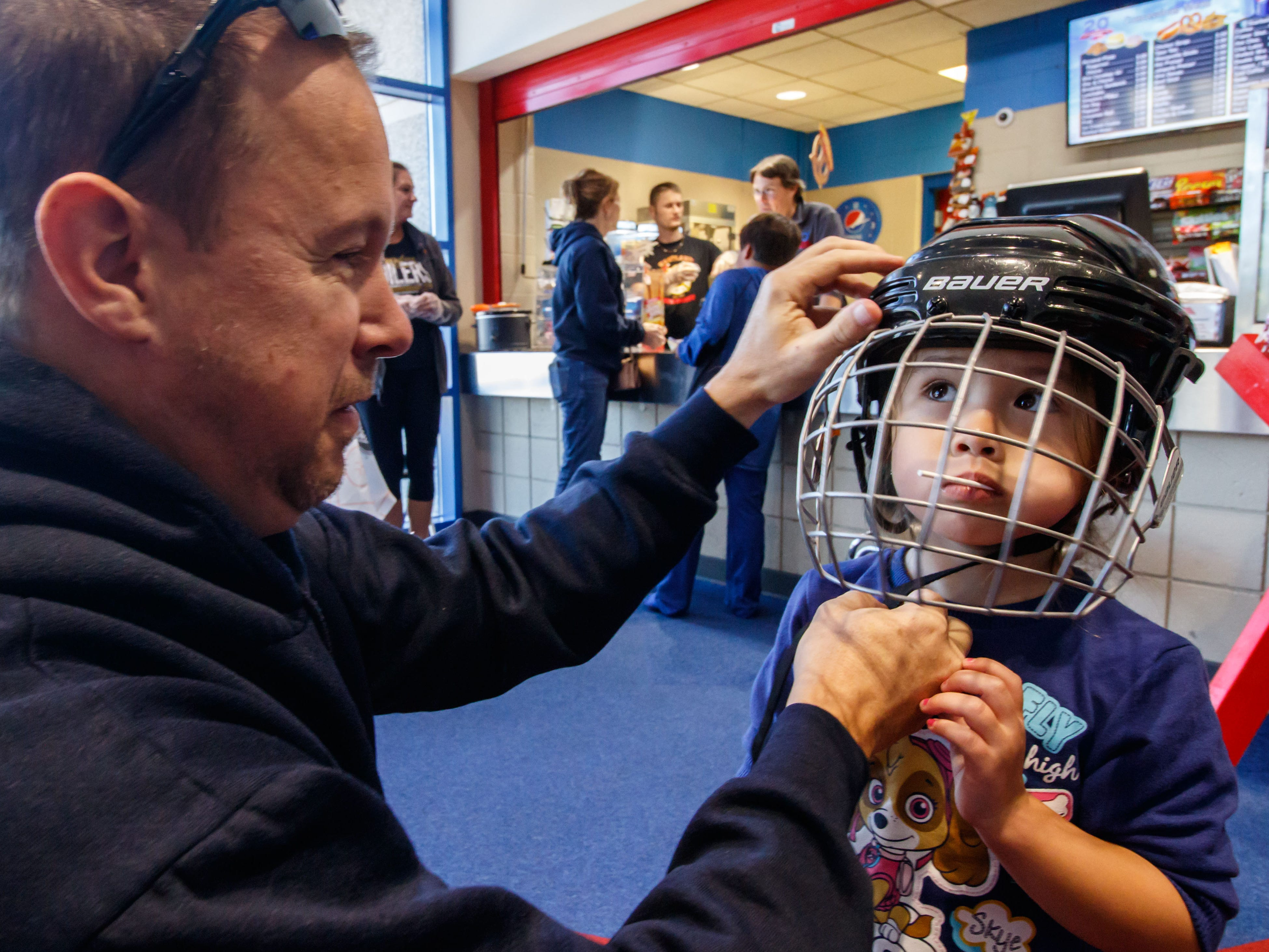 Three-year-old Anna Hodgson of Wales enjoys a lollipop while her father Sean fits her for a hockey helmet during the Mullett Ice Center's 20th anniversary open house celebration on Sunday, Sept. 23, 2018. The event featured free public skating, speed and figure skating demonstrations, open ice times for hockey, Eisstock and more.