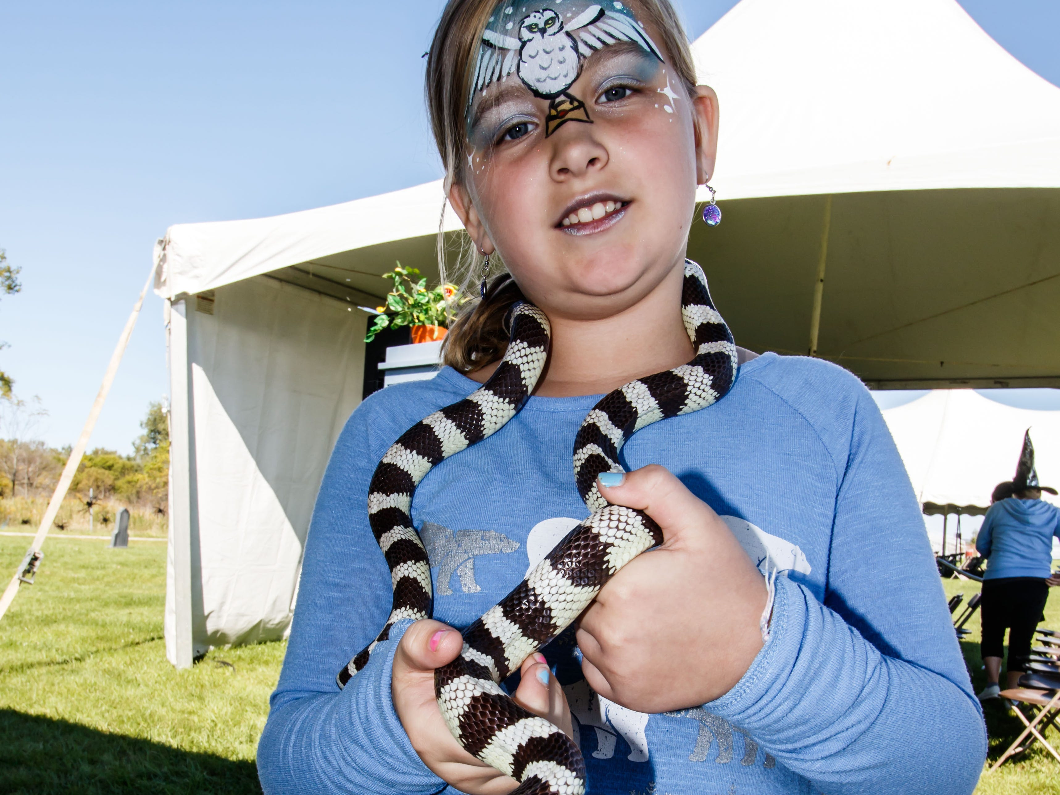 Lydia Templen, 10, of Dubuque, Iowa stops by the Snake Encounter booth during the Midwest Magic Fest at the Waukesha Expo Center on Sunday, Sept. 23, 2018. The family friendly event featured one-of-a-kind entertainment, mythical creatures, games, crafts, vendors, unique photo-ops, costume contests and much more.
