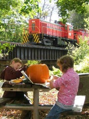 Children carve pumpkins as the Pumpkinliner rides by at the 18th Annual Pumpkin Festival at the Whippany Railway Museum on Oct. 7, 2018.