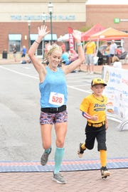 Laura-Ashley Cuthill completes the Hendersonville Half Marathon with encouragement from Johnny Cuthill at The Streets of Indian Lake on Saturday, Sept. 22.