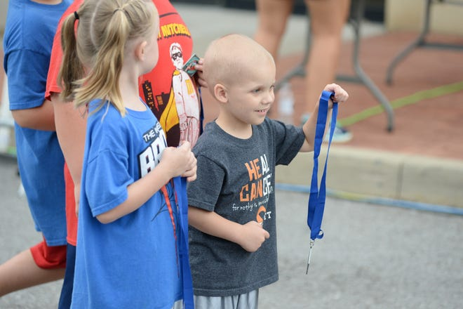 Everett Kondus waits at the finish line with a medal for the Hendersonville Half Marathon at The Streets of Indian Lake on Saturday, Sept. 22.