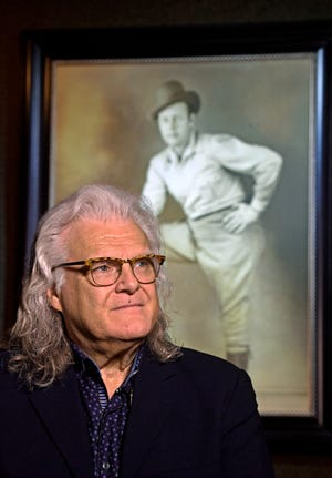 Ricky Skaggs poses in front of a portrait of Bill Monroe, an influence in Skaggs' life, on Sept. 19, 2018, in Hendersonville, Tenn. Just before Monroe died in 1996, Skaggs promised him he would do his part to keep Monroe's legacy — bluegrass music — alive.