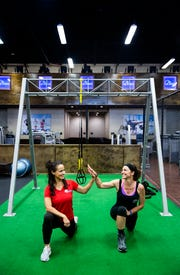 Alice Skaff, 54, high fives trainer Tanya Borrero-Borreli as they stretch together following her workout at Around the Clock Fitness in Fort Myers on Sunday, Sept. 23, 2018. Skaff is training to climb Mt. Kilimanjaro from October 3rd to the 9th to raise money for her nonprofit that helps raise the quality of orphanages in developing countries around the world.