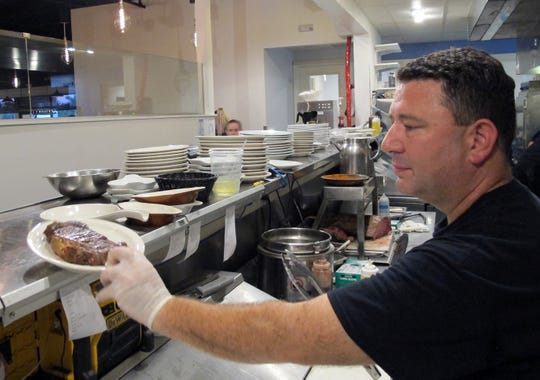 "Executive chef-owner Bernie ""BJ"" Zarvis plates an order of prime rib in the kitchen of The Pewter Mug North, which recently relocated and relaunched on U.S. 41 in North Naples."