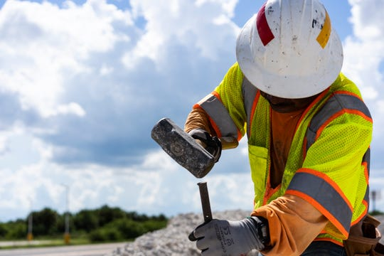 Guan Lux, a worker with Cougar Cutting Inc. from Fort Myers, hammers an iron rod into the ground Thursday, Sept. 20, 2018, to form a framing curve for improvements in Sate Road 80, which runs through Clewiston.