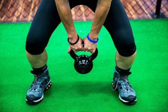 Alice Skaff, 54, does kettlebell swings while wearing her hiking boots during a training session at Around the Clock Fitness in Fort Myers on Sunday, Sept. 23, 2018. Skaff is training to climb Mt. Kilimanjaro from October 3rd to the 9th to raise money for her nonprofit that helps raise the quality of orphanages in developing countries around the world.