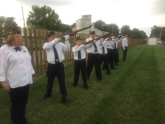 American Legion Post 107 members fire one of several volleys last Friday night to close the ceremony honoring POW/MIAs.