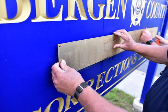 Bergen County Sheriff Officers assigned to the Maintenance Division use a screw driver to remove and flip the name plate of Michael Saudino, who retired on Friday as Sheriff of Bergen County, from the sign in front of the Bergen County Jail in Hackensack, on Monday morning on September 24, 2018.