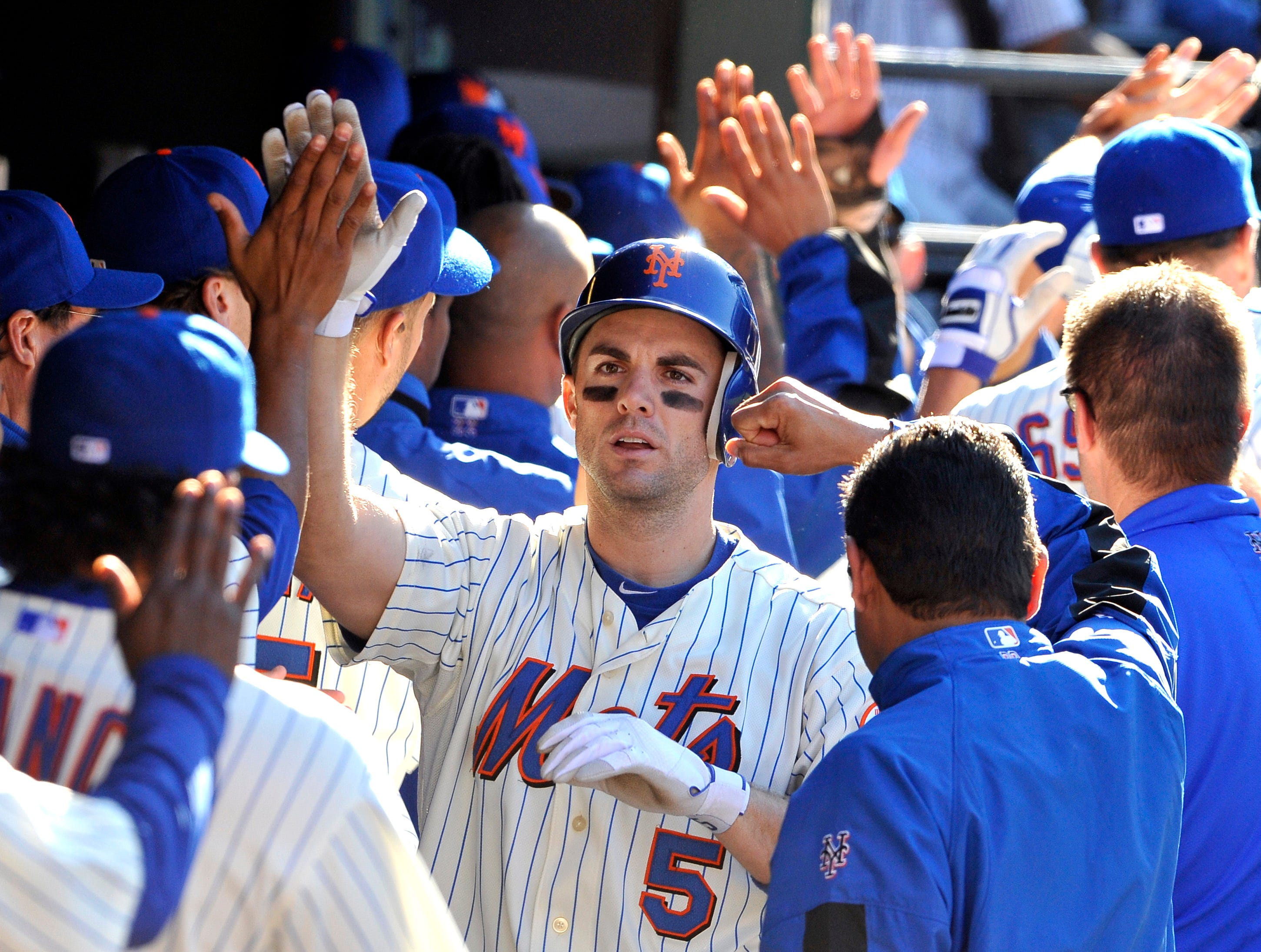 New York Mets' David Wright (5) is greeted in the dugout by teammates after hitting a three-run home run off of Washington Nationals' Tyler Clippard in the seventh inning of a baseball game Saturday, Oct. 2, 2010, in New York.