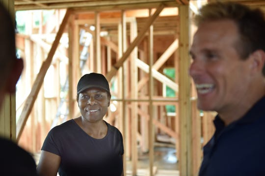 Betty Adams, at left, talks to contractors while her house in Hawthorne is being rebuilt after a fire gutted it.