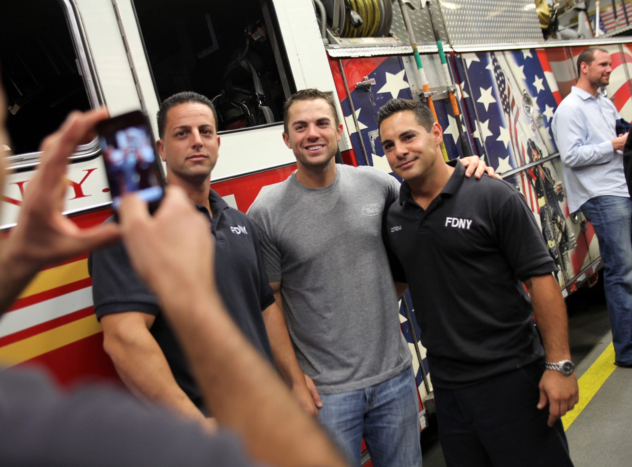 69623 New York 9/10/2010 METS WITH NYFD: Fire fighters Frank Sansonetti, left, and Sal Cotrona (cq), right pose for photos with David Wright of the Mets  during his visit to Ladder 10, Engine 10 (or the 10 house) in lower Manhattan Friday afternoon.