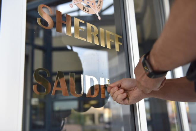 A Bergen County Sheriff Officer assigned to the Maintenance Division uses a razor blade to peel off the name of Michael Saudino, who resigned on Friday as Sheriff of Bergen County, in gold letters from the glass entrance of the Bergen County Jail in Hackensack, on Monday morning on September 24, 2018.