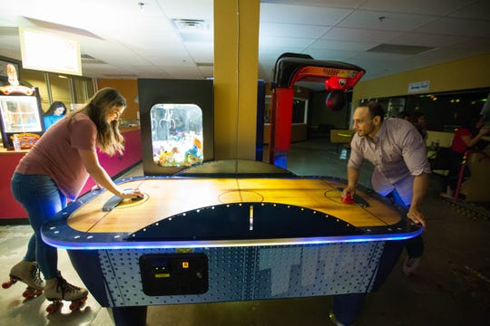 While still wearing roller skates, Darcy Horst, left, and Mundo Castaneda play air hockey on a date at The Spot Family Entertainment Center,  170 W. Picacho Ave.