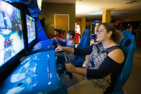 Aaron Mo rales, 8, plays a racing video game with his mom, Rosie Morales, at The Spot Family Entertainment Center on Friday, Sept.21.