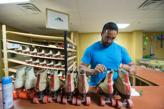 Matthew Skaria reties laces of roller skates after cleaning them on Friday, Sept. 21.