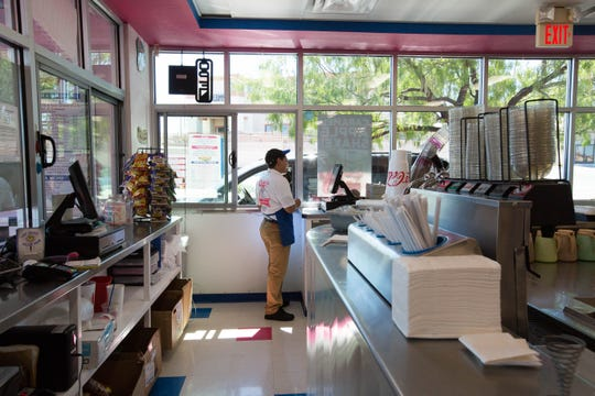 Employee Rome Silva helps a drive-through customer at Caliche's Frozen Custard, 131 N. Roadrunner Parkway in Las Cruces, on Monday, Sept. 24, 2018.