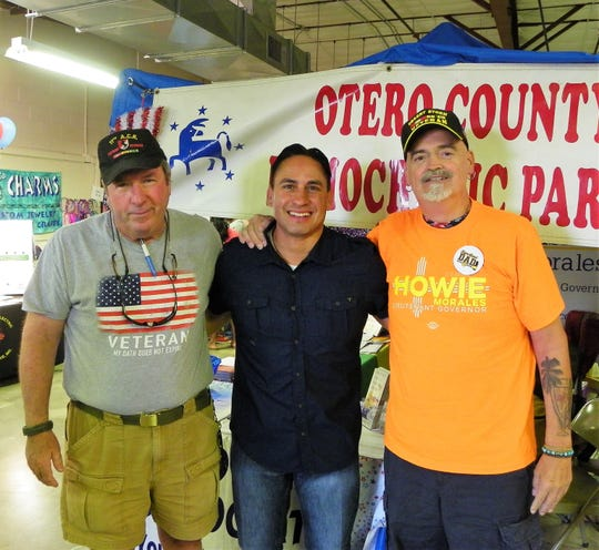 From left Mark Praught, Howie Morales and Dan Stump stand in front of the Otero County Democrats booth at the Otero County Fair Saturday.