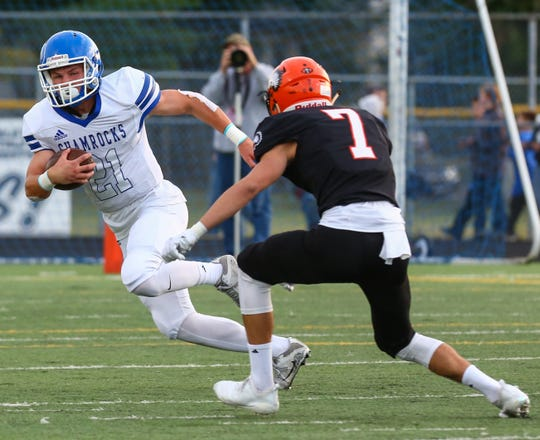 Catholic Central's Keegan Koehler (left) tries to shake Brother Rice tackler Rocco Milia during Saturday's Central Division tussle.