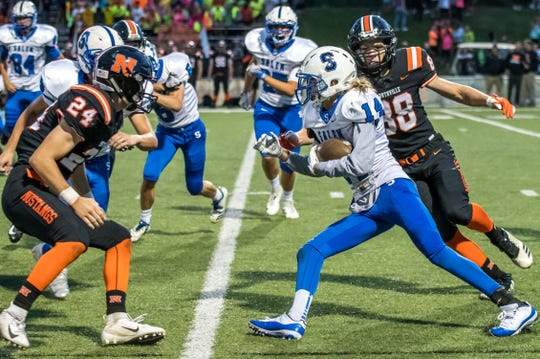 Salem's Sheldon Lyall (14) tries to split Northville tacklers Josiah Bowers (right) and Spencer Ziparo (24).