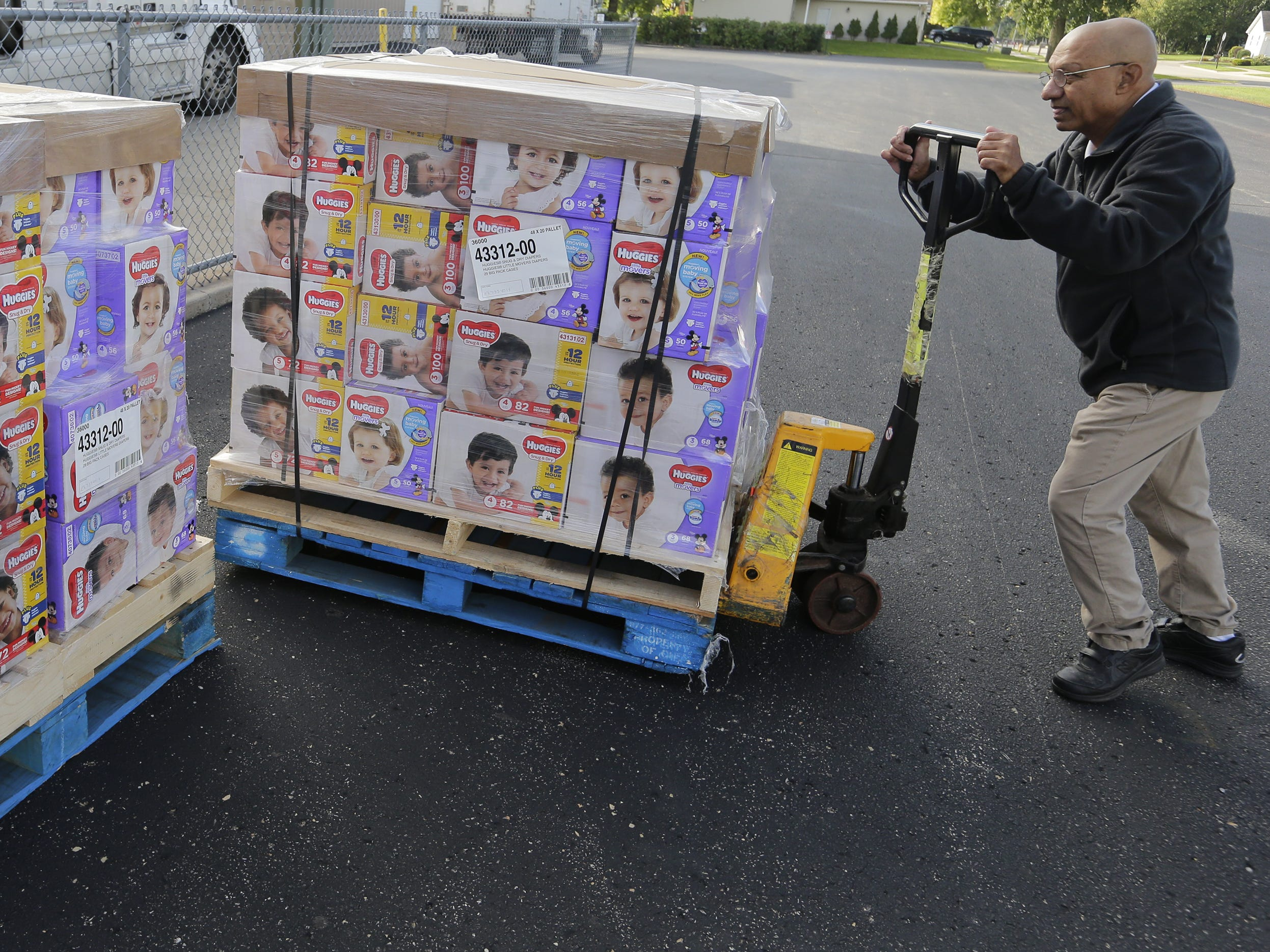 Hussain Sattar of Father Carr's Food Pantry helps position the pallets of diapers to be distributed. The Oshkosh Area Community Food Pantry gets a donation of 50 pallets with 100,400 diapers on them from the USA TODAY NETWORK and Kimberly-Clark Corp. on Monday, Sept. 24, 2018, in Oshkosh. The diapers will go to nine food pantries in the area.